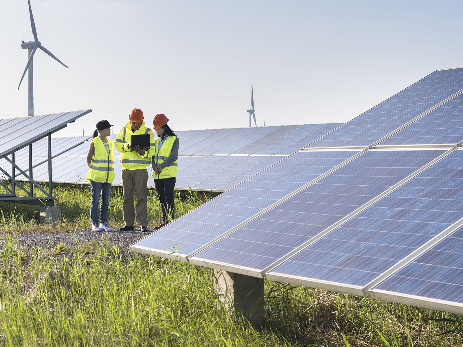 ingenieros trabajando en instalación de energía solar y eólica
